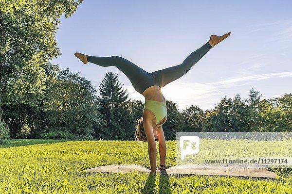 Handstand,  Junge Frau in Sportkleidung trainiert auf einer Matte in der Wiese in einem Park,  München,  Oberbayern,  Bayern,  Deutschland,  Europa