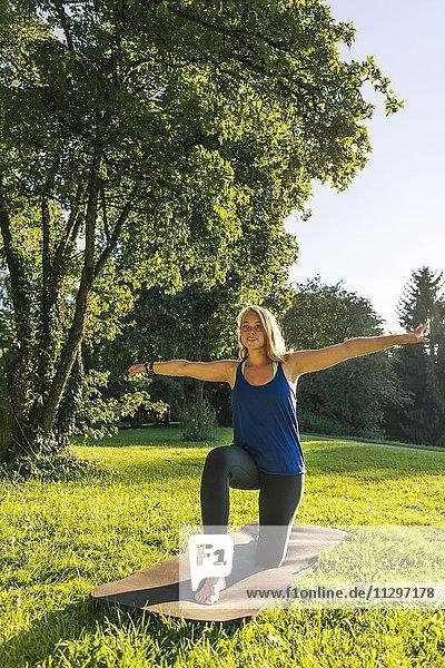 Aufwärmübung  Junge Frau in Sportkleidung trainiert auf einer Matte in der Wiese in einem Park  München  Oberbayern  Bayern  Deutschland  Europa