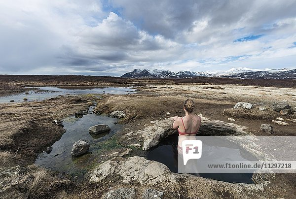 Young woman in hot spring looking towards mountains  Eyjar og Miklaholt  Western Region  Iceland  Europe