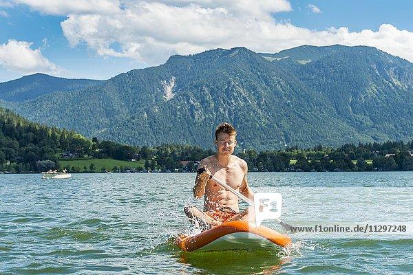 Junger Mann sitzt auf einem Board  Stand-Up-Paddel oder SUP auf einem See  Schliersee  Oberbayern  Bayern  Deutschland  Europa
