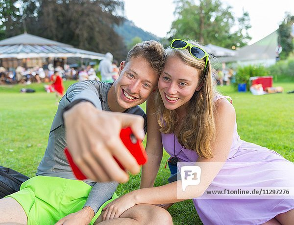 Junger Mann und junge Frau lächelt  fotografiert sich mit einem Handy selbst  Selfie  Bayern  Deutschland  Europa