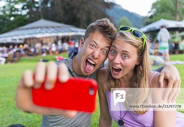 Junger Mann und junge Frau ziehen Grimasse  fotografiert sich mit einem Handy selbst  Selfie  Bayern  Deutschland  Europa