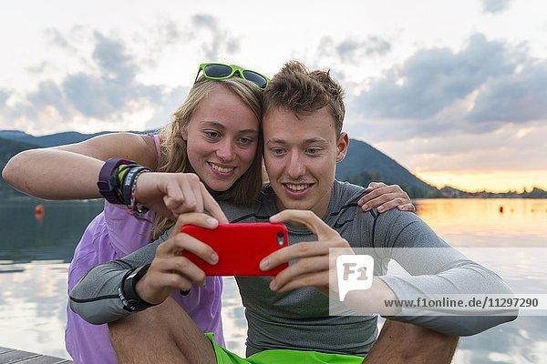 Junges Paar schaut in ein Handy zusammen  Schliersee  Oberbayern  Bayern  Deutschland  Europa