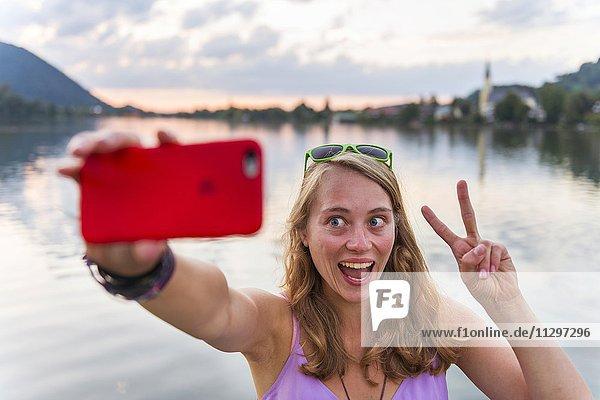 Junge Frau lacht und macht V-Zeichen  fotografiert sich mit einem Handy  Selfie  Schliersee  Oberbayern  Bayern  Deutschland  Europa