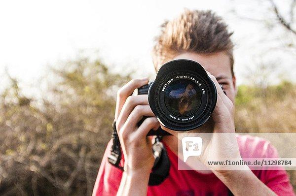 Junge fotografiert mit einer Spiegelreflexkamera