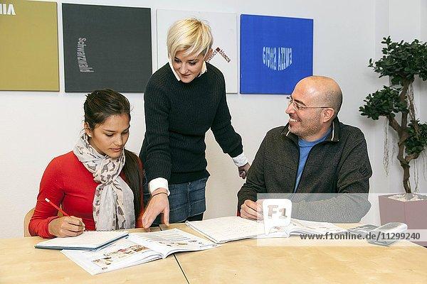 Lehrerin zeigt Schülerin etwas im Buch  Deutschkurs in einer Sprachschule  Düsseldorf  Nordrhein-Westfalen  Deutschland  Europa