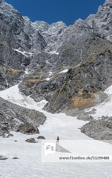 Wanderin steht auf Stein  tiefstes Schneefeld der Deutschen Alpen  Watzmann Ostwand  Berchtesgaden  Bayern  Deutschland  Europa