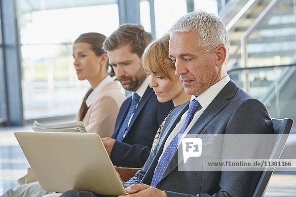 Geschäftsmann bei der Arbeit mit dem Laptop im Abflugbereich des Flughafens