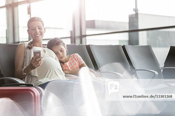 Schwangere Mutter mit Handy und schlafender Tochter im Abflugbereich des Flughafens