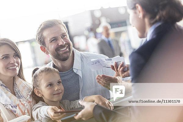 Kundenbetreuerin hilft der Familie mit Tickets am Flughafen-Check-in-Schalter Kundenbetreuerin hilft der Familie mit Tickets am Flughafen-Check-in-Schalter
