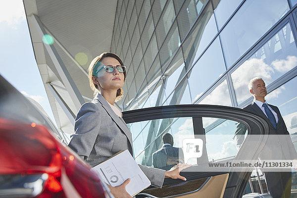 Geschäftsfrau,  die am Flughafen ankommt und aus dem Stadtauto aussteigt.