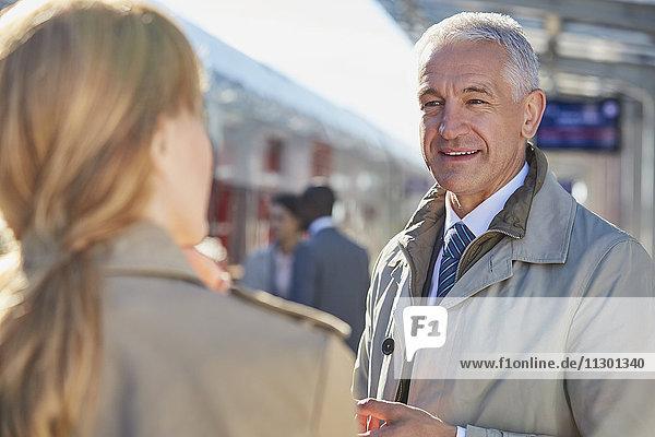 Geschäftsmann im Gespräch mit Geschäftsfrau am Bahnsteig