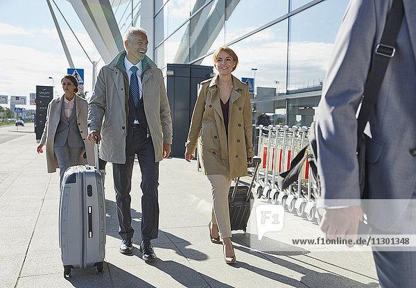 Geschäftsleute  die außerhalb des Flughafens an Koffern ziehen.