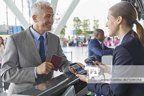 Kundendienstmitarbeiter scannt Smartphone QR-Code Bordkarte am Check-in-Schalter am Flughafen
