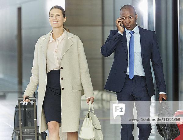 Geschäftsleute mit Gepäck in der Flughafenhalle