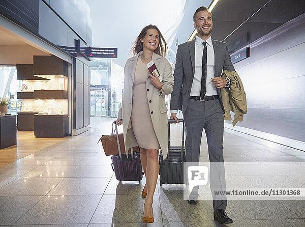 Geschäftsleute beim Kofferziehen in der Flughafenhalle