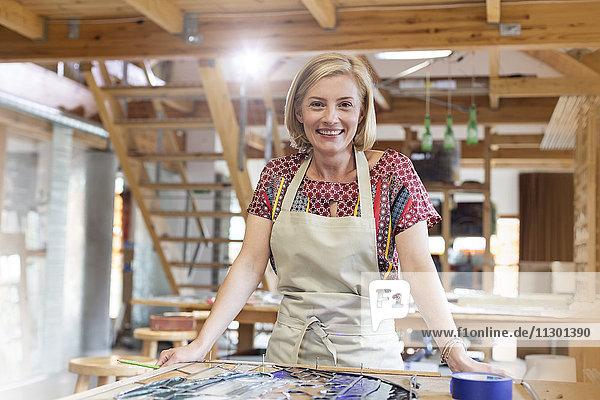 Portrait lächelnder Glasmaler bei der Arbeit im Atelier