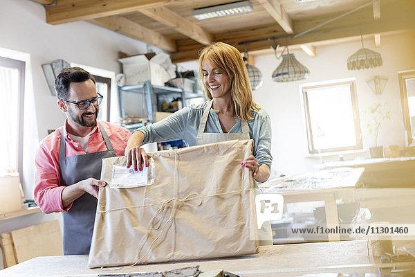 Lächelnde Künstler verpacken Glasmalereiprojekt im Atelier