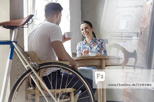 Ein Paar trinkt Kaffee und redet bei Tisch.