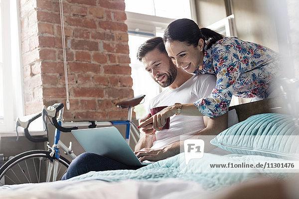 Paar Kaffee trinken mit Laptop im Bett