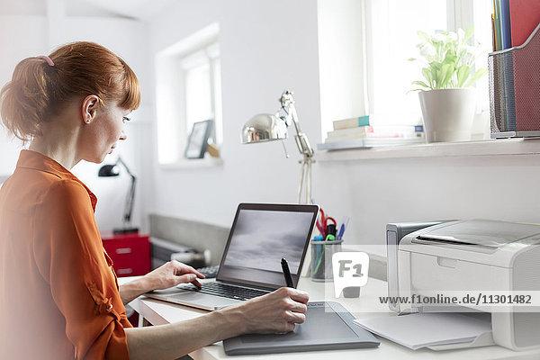 Designer mit Grafiktablett am Laptop im Büro