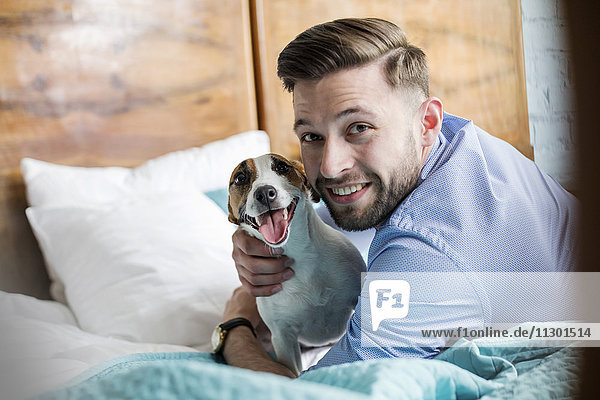 Portrait smiling man petting Jack Russell Terrier dog on bed