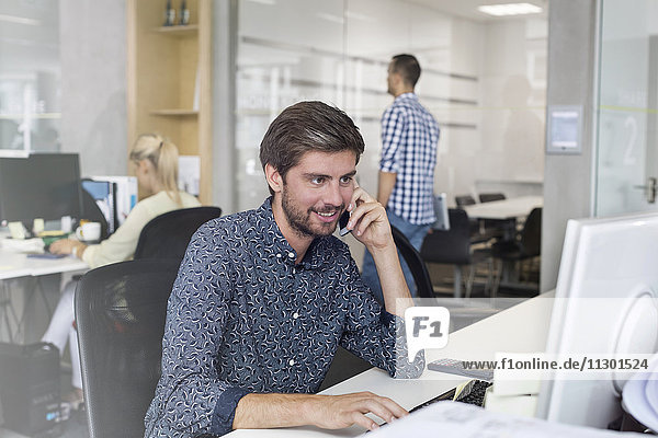 Geschäftsmann beim Telefonieren am Computer im Büro