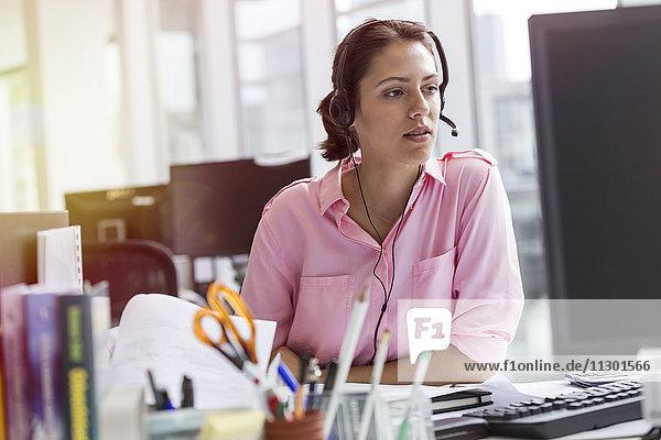Geschäftsfrau mit Freisprecheinrichtung am Computer im Büro
