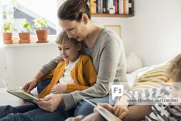 Mutter liest Bilderbücher für die Tochter zu Hause.