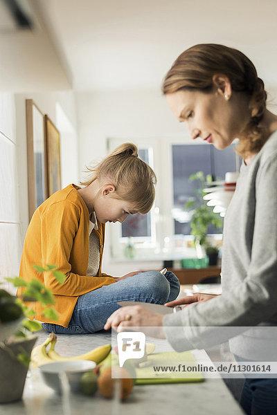 Frau schneidet Früchte mit einem Mädchen  das zu Hause auf der Küchentheke sitzt.