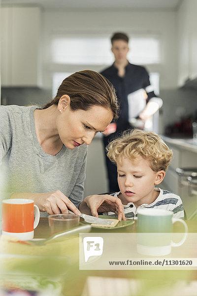 Frau beim Frühstücken im Wohnzimmer zu Hause