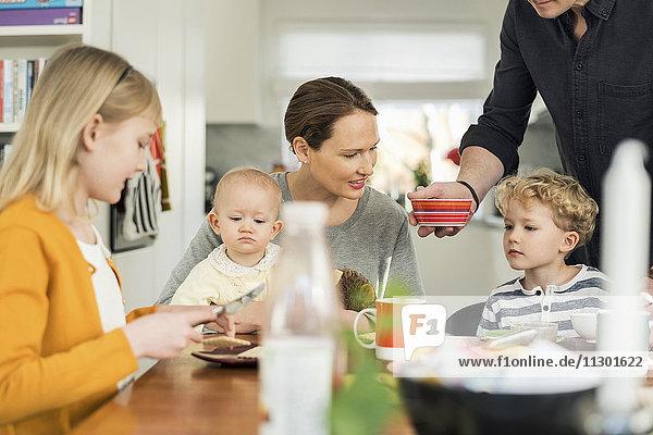 Familienfrühstück am Tisch im Wohnzimmer