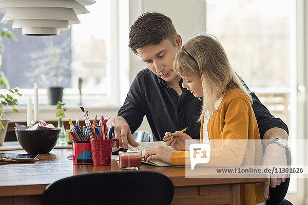 Vater hilft der Tochter bei den Hausaufgaben zu Hause