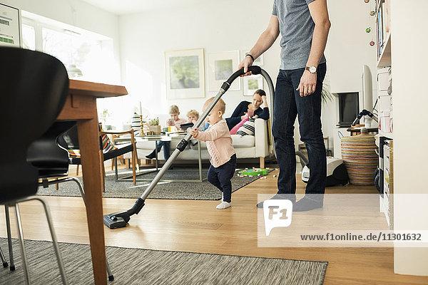 Niedriger Bereich von Mensch und Kleinkind Reinigung Boden mit Staubsauger zu Hause