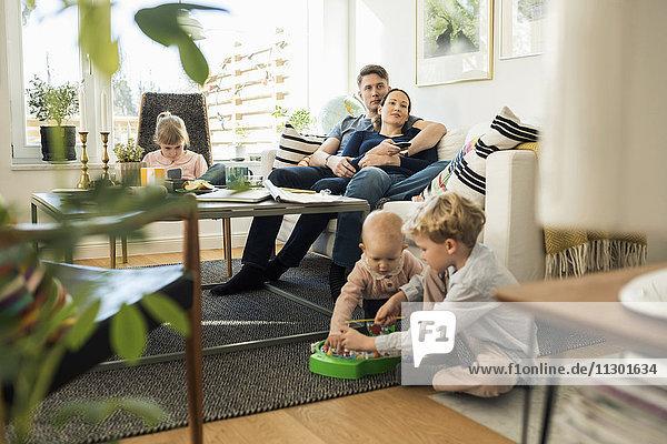 Kinder spielen mit den Eltern auf dem Sofa zu Hause