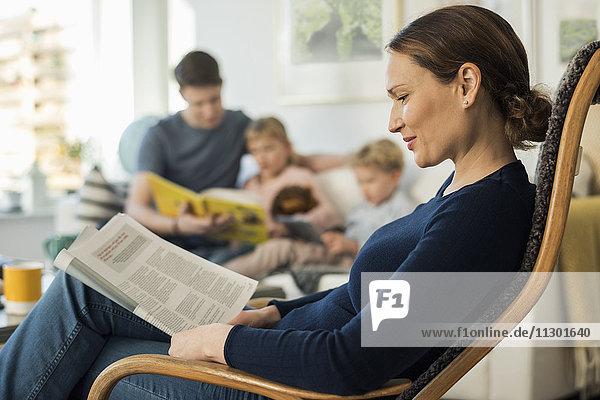 Mutter Lesedokument auf Stuhl mit Familie im Wohnzimmer sitzend