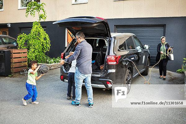Vater spielt mit Kindern  während die Mutter das elektrische Ladegerät mit dem Auto rollt.