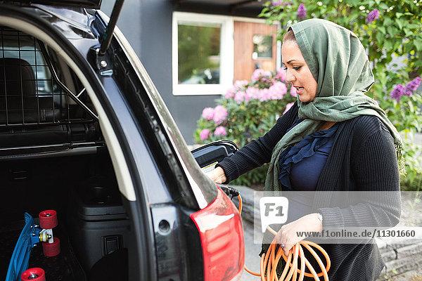 Seitenansicht der Frau  die ein Elektroauto auflädt  während sie vor dem Haus steht.