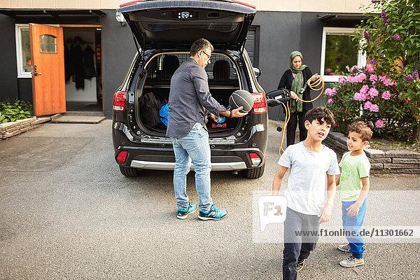 Jungen stehen  während Vater und Mutter vor dem Haus am Auto stehen.