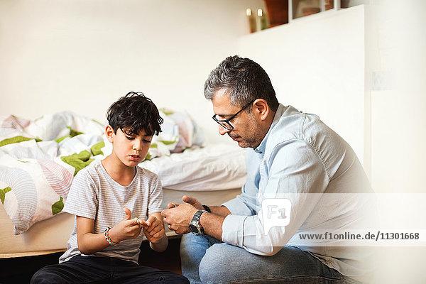 Vater und Sohn spielen mit Gummibändern am Bett zu Hause