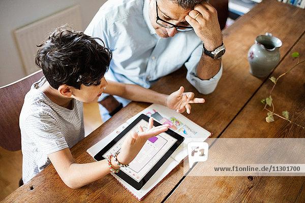 Hochwinkelansicht von Vater und Sohn  die über das digitale Tablett diskutieren  während sie zu Hause studieren.