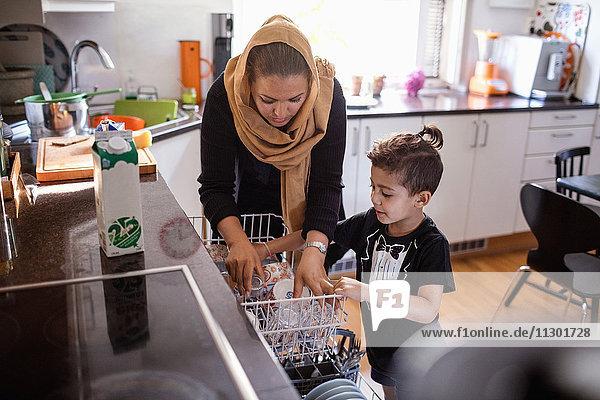 Mutter und Sohn arrangieren Utensilien im Geschirrspüler in der Küche