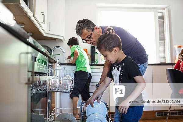 Vater und Sohn arrangieren Teller in der Spülmaschine in der Küche