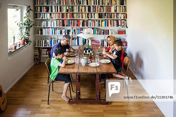 Familie beim Essen am Esstisch im Bücherregal