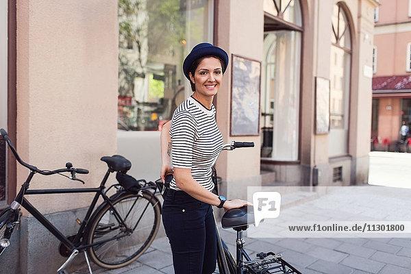 Seitenansicht Porträt einer glücklichen Frau mit Fahrrad auf dem Bürgersteig