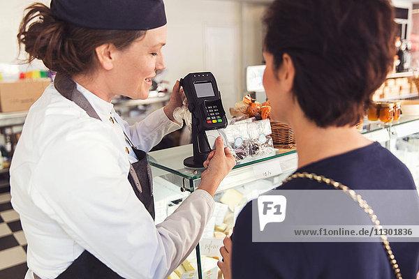 Verkäuferin unterstützt Kundin mit Kreditkartenleser im Lebensmittelgeschäft