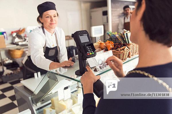 Verkäuferin beim Betrachten der weiblichen Kundin im Kreditkartenleser im Lebensmittelgeschäft