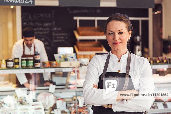 Porträt eines selbstbewussten Besitzers  der im Hintergrund im Lebensmittelgeschäft arbeitet.