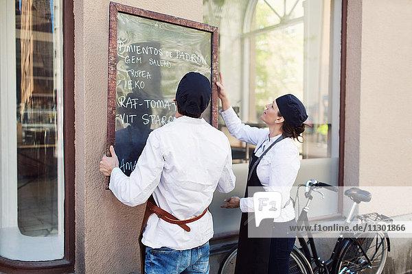 Männliche und weibliche Besitzer  die eine Tafel an der Wand außerhalb des Lebensmittelladens anbringen.