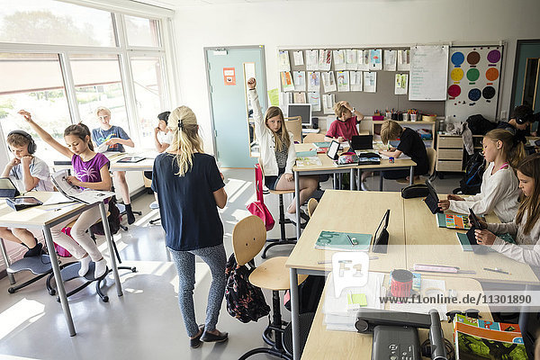 High school students raising hands with teacher in classroom